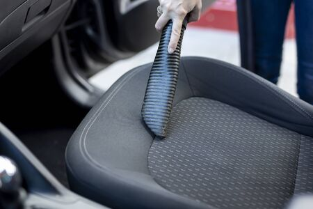 Detail of female hand holding a vacuum cleaner and vacuuming car seats and interior