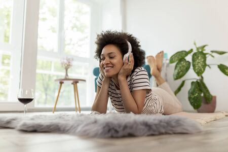 Beautiful young mixed race woman lying on the living room floor, listening to the music, drinking wine and enjoying leisure time at home Stockfoto