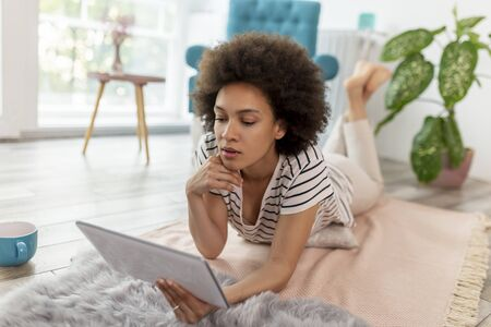 Female blogger lying on the living room floor, writing a new blog post, working remotely from home
