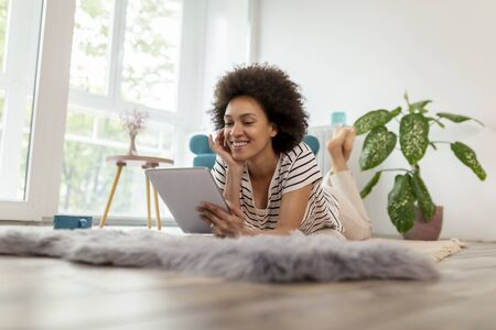 Beautiful young mixed race woman lying on the living room floor, having a video call on a tablet computer; woman enjoying her leisure time activities at home Stockfoto