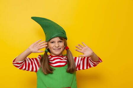 Beautiful little girl in Santa helper costume smiling and waving isolated on yellow colored background