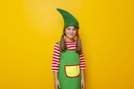 Portrait of a beautiful little girl in Santa helper costume isolated on yellow colored background; child dressed as a Christmas elf smiling and having fun Stockfoto - 130478437