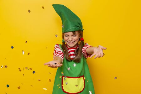 Portrait of a beautiful little girl dressed as a Christmas elf, having fun while throwing colorful confetti on yellow colored background Stockfoto - 130478439