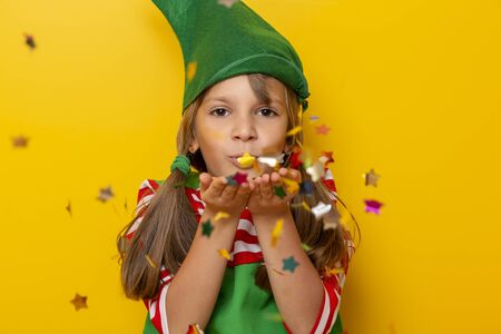 Portrait of a beautiful little girl wearing Christmas elf costume, having fun while blowing colorful star-shaped confetti on yellow colored background