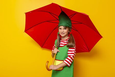Beautiful little girl wearing Christmas elf costume holding an opened red umbrella isolated on yellow colored background Stockfoto