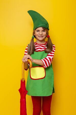 Beautiful little girl wearing Christmas elf costume holding a closed red umbrella isolated on yellow colored background Stockfoto - 130478513