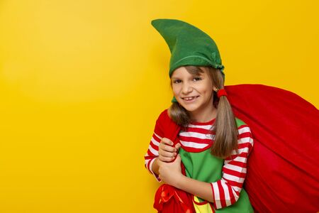 Portrait of a beautiful cheerful little girl dressed as Santa helper, carrying a big sack filled with Christmas presents, isolated on yellow colored background Stockfoto