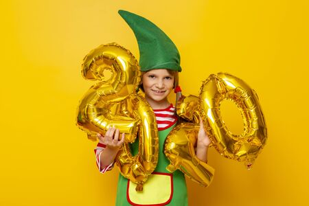 Beautiful little girl wearing Christmas elf costume holding golden balloons shaped as numbers 2020, isolated on yellow colored background Stockfoto