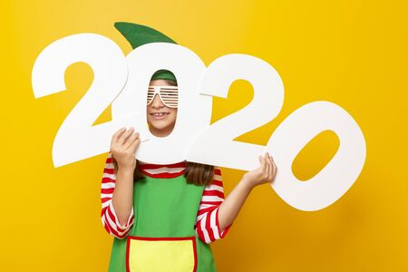Portrait of a beautiful little girl dressed as Christmas elf wearing party glasses, holding numbers 2020, isolated on yellow colored background Stockfoto - 130478515
