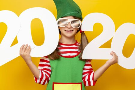 Portrait of a beautiful little girl dressed as Christmas elf wearing party glasses, holding numbers 2020, isolated on yellow colored background Stockfoto - 130478525