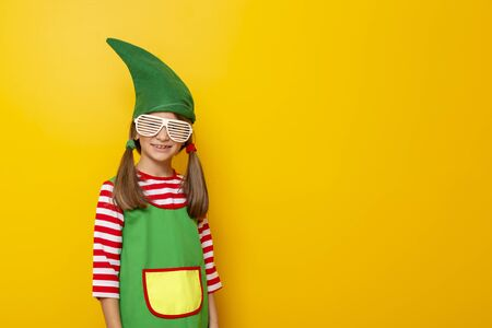 Portrait of a beautiful little girl wearing Christmas elf costume and party glasses on yellow colored background with copy space Stockfoto - 130478524