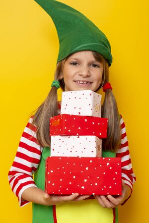 Beautiful little girl dressed as Santas helper holding a pile of nicely wrapped Christmas presents isolated on yellow colored background