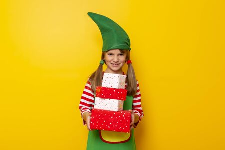 Beautiful little girl dressed as Santas helper holding a pile of nicely wrapped Christmas presents isolated on yellow colored background Stockfoto - 130478526