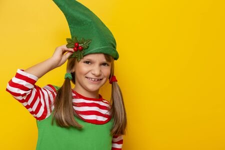 Portrait of a beautiful cheerful little girl dressed as a Christmas elf, holding a mistletoe, isolated on yellow colored background with copy space