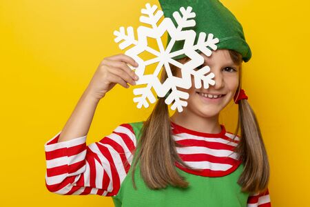 Portrait of a beautiful little girl in elf costume holding a giant white cardboard snowflake and smiling, isolated on yellow colored background Stockfoto - 130478530