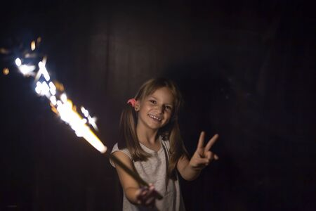 Beautiful little girl having fun while holding and waving with a sparkler on Christmas Eve