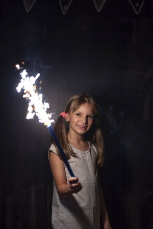 Portrait of a beautiful little girl having fun while holding a sparkler on Christmas Eve