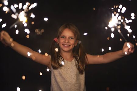 Portrait of a beautiful little girl having fun while holding and waving with sparklers on Christmas Eve