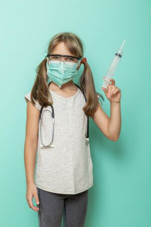 Beautiful little girl wearing surgical mask, stethoscope and protective lab glasses holding a giant syringe; child role-playing a doctor or nurse