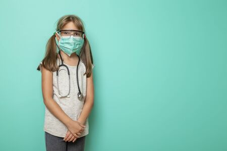 Beautiful little girl wearing surgical mask, stethoscope and protective lab glasses on mint colored background; child role-playing a doctor or nurse
