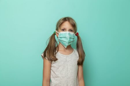 Little girl wearing surgical mask as a flu infection protection on mint colored background or prevention of spreading of influenza virus