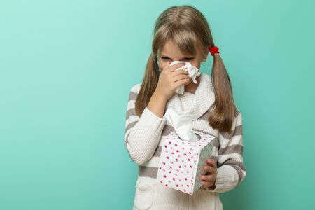 Portrait of a beautiful little girl crying, holding a paper tissue box and wiping tears
