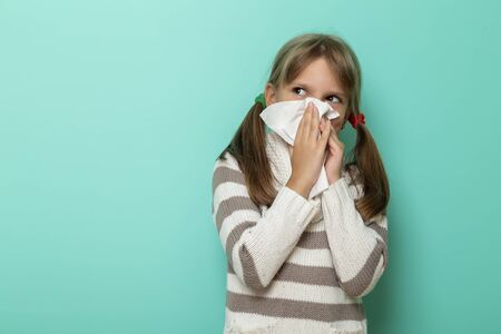 Portrait of a little girl having a flu, blowing and wiping nose with paper tissues on mint colored background Stockfoto