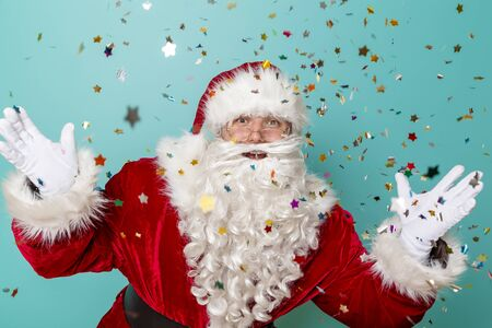 Santa Claus celebrating New Year and having fun, isolated on mint colored background with colorful confetti all around