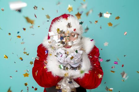 Santa Claus blowing colorful confetti, celebrating New Year and having fun, isolated on mint colored background