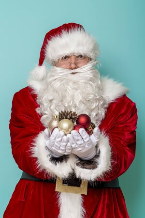 Portrait of Santa Claus holding a handful of Christmas tree decorations isolated on mint colored background Stockfoto