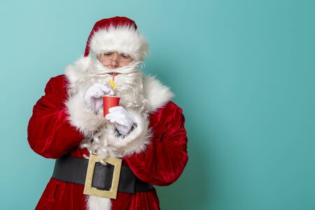 Santa Claus drinking cocktail on mint colored background with copy space