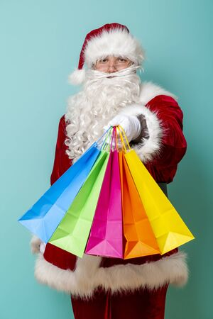 Portrait of Santa Claus doing shopping during winter seasonal sales, carrying bunch of colorful shopping bags isolated on mint colored background