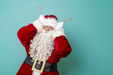 Santa Claus having fun holding candy cane antlers isolated on mint colored background with copy space
