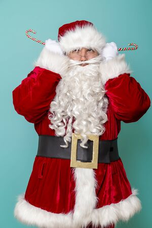 Santa Claus having fun holding candy cane ears isolated on mint colored background