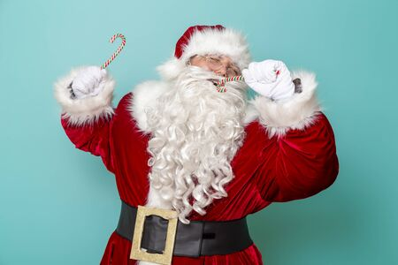 Santa Claus having fun singing karaoke on candy cane mike isolated on mint colored background Stockfoto
