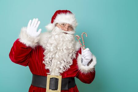 Santa Claus holding candy canes and waving to the camera, isolated on mint colored background