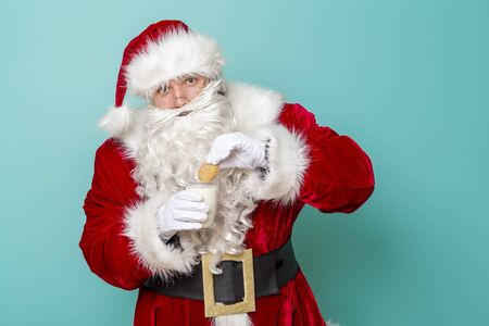 Portrait of Santa Claus drinking milk and eating cookies on Christmas Eve isolated on mint colored background Stockfoto