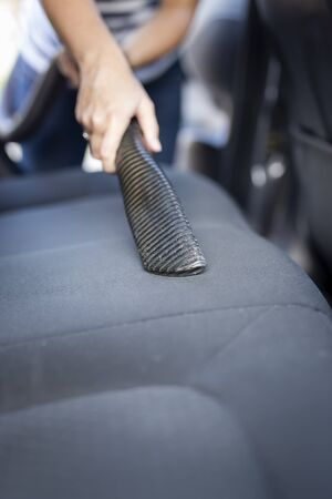 Detail of female hand holding a vacuum cleaner and vacuum-cleaning car seats and interior