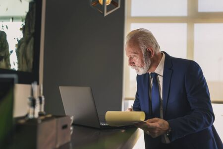 Senior businessman in a modern office working on a laptop computer and taking notes, pensive and serious Stockfoto