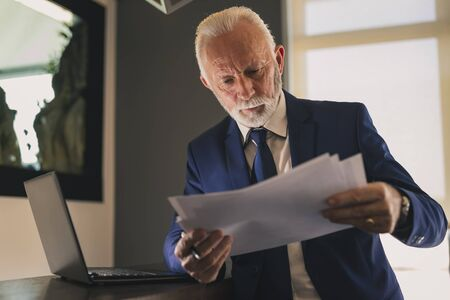 Senior businessman in a modern office working on a laptop computer and analyzing contracts and documentation, serious and pensive Stockfoto