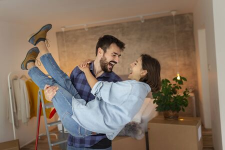 Beautiful newly married young couple moving in together, having fun while unpacking cardboard boxes with their belongings, husband carrying wife in his arms 版權商用圖片