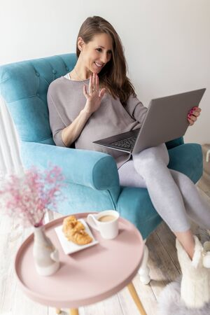 Pregnant woman sitting in an armchair and having a video call on her laptop computer