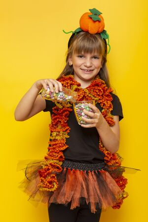 Little girl wearing a Halloween witch costume, pouring colorful candies from a bottle into a glass, happy after trick or treat adventure