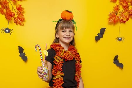 Little girl dressed as a witch holding a bottle filled with colorful candies for Halloween trick or treat on yellow colored background