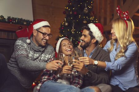 Group of friends sitting on the floor next to a nicely decorated Christmas tree and making a toast with glasses of champagne on New Years Eve home party