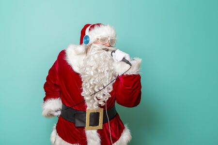 Santa Claus having fun wearing a headset, listening to the music, dancing and singing karaoke on mike isolated on mint colored background