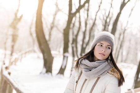 Hermosa joven de pie al aire libre serio y pensativo, disfrutando de un hermoso día de invierno cubierto de nieve en la naturaleza