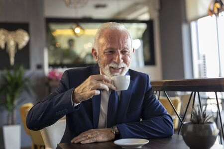 Senior businessman on coffee break in a restaurant, having a conversation with business partner and drinking coffee
