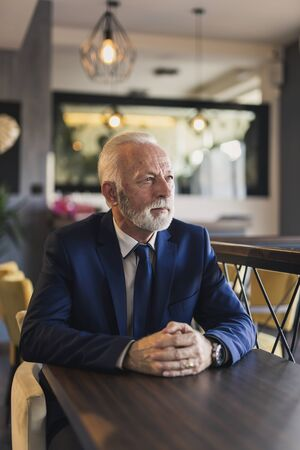 Portrait of a pensive senior businessman sitting in a modern office building restaurant, taking a coffee break and looking at the distance