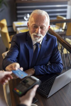 Senior businessman sitting at a restaurant table, paying the bill by offering his credit card to a restaurant employee Stok Fotoğraf